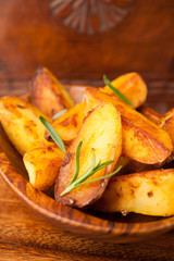 Potato Wedges with rosemary in wooden bowl
