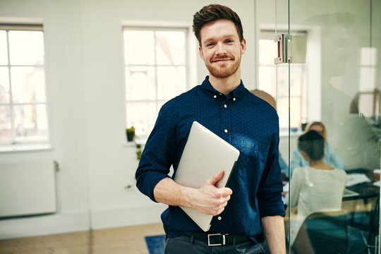 Smiling young businessman standing with his laptop at work