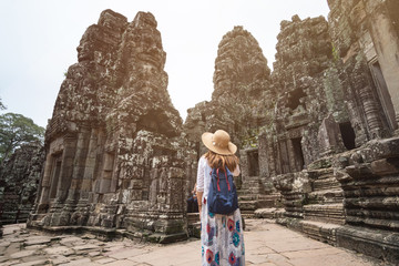 Young woman traveler visiting in Bayon temple at Angkor Wat complex, Khmer architecture heritage in Siem Reap, Cambodia