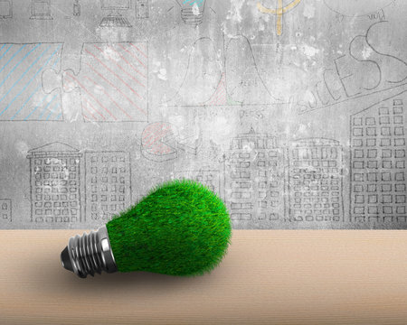 Light bulb with green grass on the wooden table and doodles concrete wall background, ECO green energy concept.