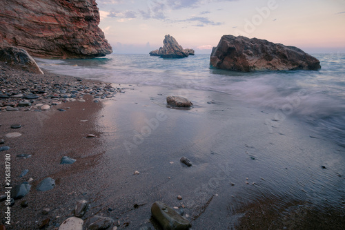 Rocky beach seascape at sunset time  Wet sand on a surf line