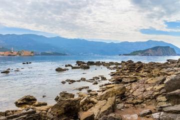 Mogren beach with big stones, old city Budva and Sveti Nikola island at Adriatic sea coastline in Montenegro