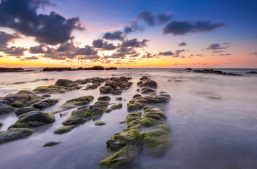 view of beautiful sunset at the beach with natural coastal rocks covered by green moss. soft focus due to slow shutter effect.