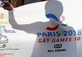 A man displays a banner as he participates at the international Rainbow Memorial Run during the inauguration of the Gay Games village at the Hotel de Ville city hall in Paris
