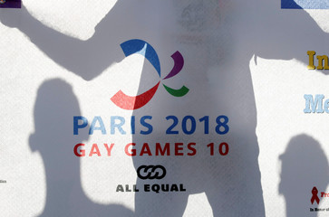 People display a banner as they participate at the international Rainbow Memorial Run during the inauguration of the Gay Games village at the Hotel de Ville city hall in Paris