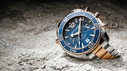 Luxury wristwatches on sand ground focused to light
