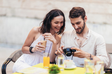 Tourist couple looking photo on camera in cafe shop