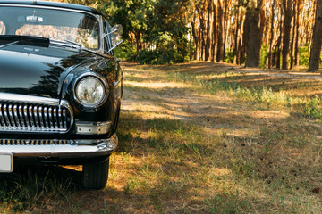 half of a black, old, vintage car with glare from the sun, which stands on a clearing in the valley on a summer day.