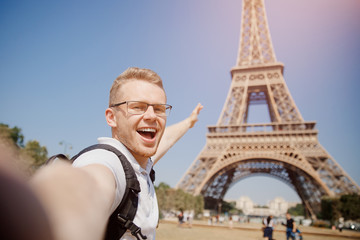 Man tourist with backpack and wearing glasses makes selfie photo on background of Eiffel Tower in Paris, France. Concept travel.
