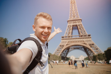 Male student doing selfie photo on background of Eiffel Tower in Paris, France. Concept travel, training, university.