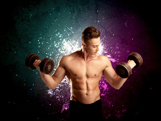 A sexy male fitness trainer showing his muscles and looking seductive with a weight in his hands in front of bright paint splash purple wall concept.