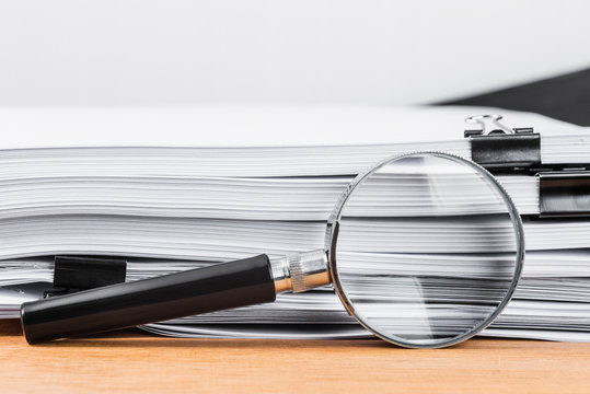 Close-up magnifying glass place on wooden table and search to edge of white documents