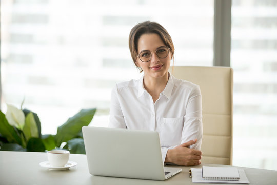 Smiling confident millennial businesswoman posing at personal desk, happy successful female ceo smiling at camera, photo portrait of business owner in small modern office workplace in business center