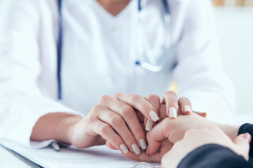 Friendly female doctor's hands holding female patient's hand for encouragement and empathy close-up. Partnership, trust and medical ethics concept.