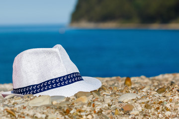 e61790e2b60 Men s hat of white color lies on stones against the background of the sea  and mountains