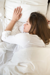 Top view of young female sleeping well on soft white pillows under linen cover or duvet, millennial woman having peaceful nap in cozy bed, relaxing in bedroom, calm girl lying asleep seeing dreams