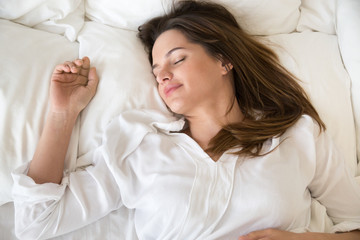 Top close up view of relaxed young female sleeping well on oft white pillows under warm fluffy duvet, calm woman resting in bedroom, being asleep seeing sweet dreams, girl taking nap in cozy bed