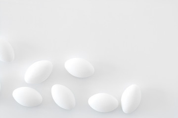 Fotobehang Macarons White pills on white background, place for text.