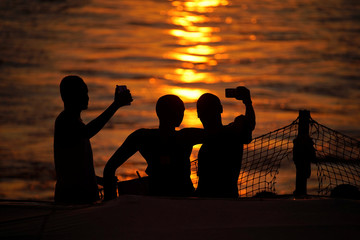 Migrants take selfies on board NGO Proactiva Open Arms rescue boat in the central Mediterranean Sea
