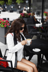 Sexy and fashionable brunette model girl with professional makeup and stylish sunglasses, in white shorts and in a white jacket sits with cup of coffee and with red clutch bag at the table in cafe