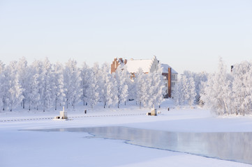 Winter scenery with frost covered trees and old building on riverbank.