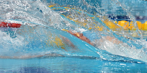 Man compete in swimming pool. Man swimming backstroke. Swimmer in swimming pool behind the water splash curtain.