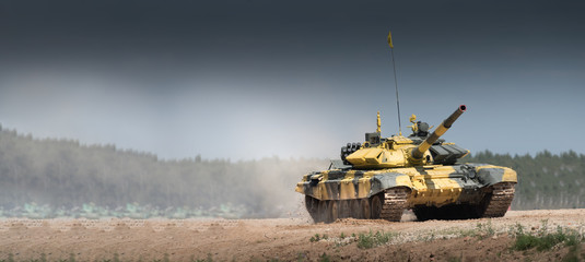 Military or army tank ready to attack and moving over a deserted battle field terrain. a lot of dust. copyspace Fototapete