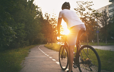 The young guy in casual clothes is cycling on the road in the evening city Wall mural