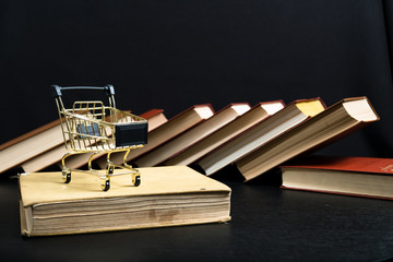 Stack of old books on a wooden shelf and shopping carts