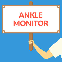 ANKLE MONITOR. Hand holding wooden sign