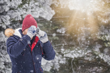 Young man with vintage photo camera in nature. Winter scene background.