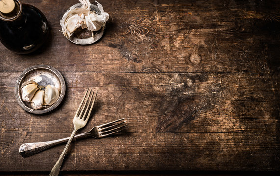 Dark rustic aged wooden food background with cutlery and seasoning, top view with copy space for your design,recipes,menu, meal or text