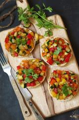 kleine Brötchenpizzen mit buntem Zucchini-Paprika Gemüse und Parmesan