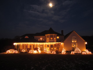 Christmas House lit up with white lights, moon in the sky