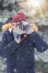 Fashionable man taking photos with retro camera on snowy day. Winter vacation travel concept.
