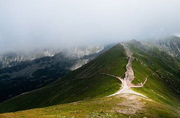 Scenic mountain view with low clouds and beautiful light at summer day in Tatra National Park, Poland