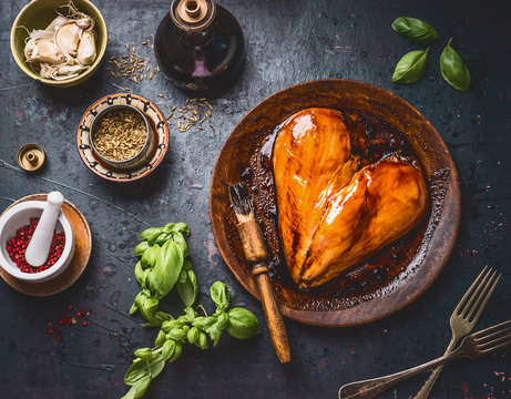 Chicken breast meat in heart shape with rub brush and marinate for cooking or grill on rustic dark background with ingredients bowls: herbs, spices and sauce, top view . Protein fitness food