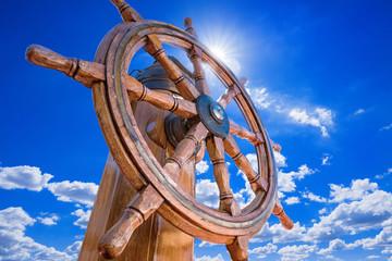 steering wheel against a sunny blue sky