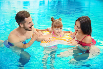 Happy family with inflatable ring in swimming pool
