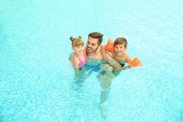 Happy father with children in swimming pool
