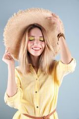 Beautiful young woman in hat on color background. Summer fashion