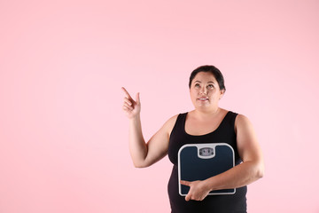 Overweight woman in sportswear with scales on color background