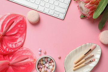 Creative flat lay composition with tropical flowers, computer keyboard and beauty accessories on color background