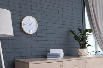 Stylish room interior with wall clock. Time of day