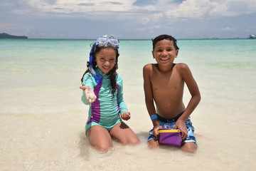 children playing on white sand beach in Boracay, Philippines
