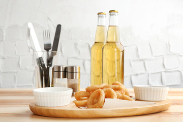 Tasty onion rings and bowls with sauces on wooden table