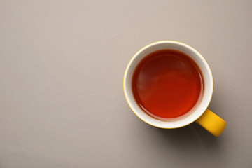 Cup of black tea on color background, top view