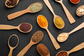 Composition with different aromatic spices in wooden spoons on dark background