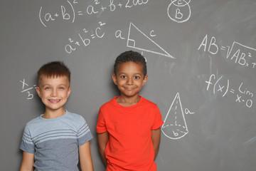 Little school children and mathematical formulas on grey background