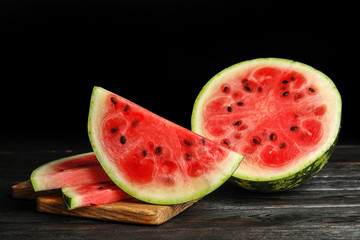 Wooden board with juicy watermelon slices on table